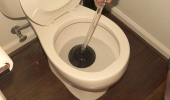 plunger in a clogged toilet that was overflowing